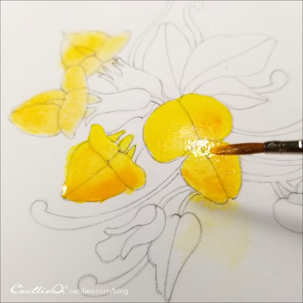 Painting yellow watercolor on the flower petals.