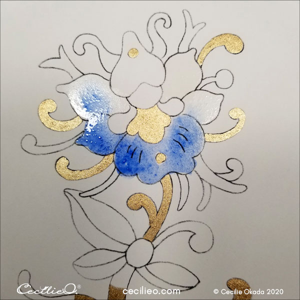 Painting blue watercolor on the flower head.