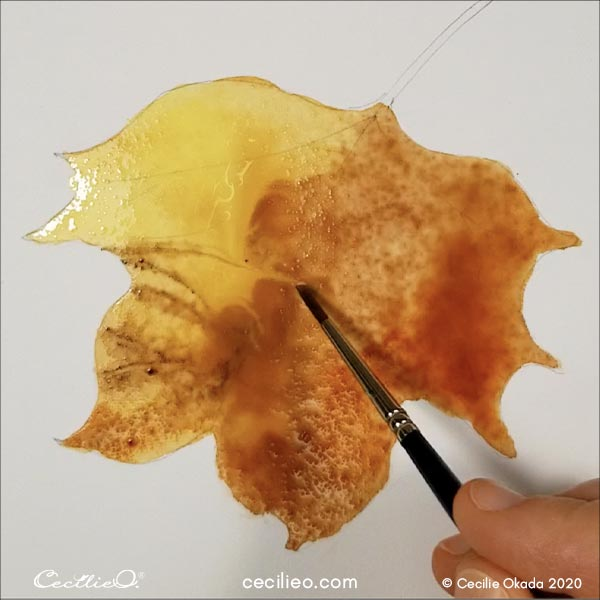 Painting the leaf with watercolor.
