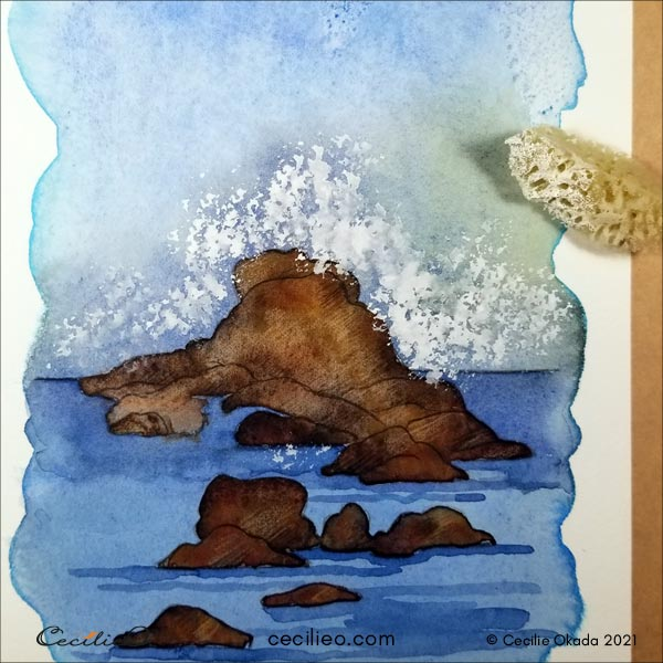 Using a natural sponge to create sea spray with white gouache.