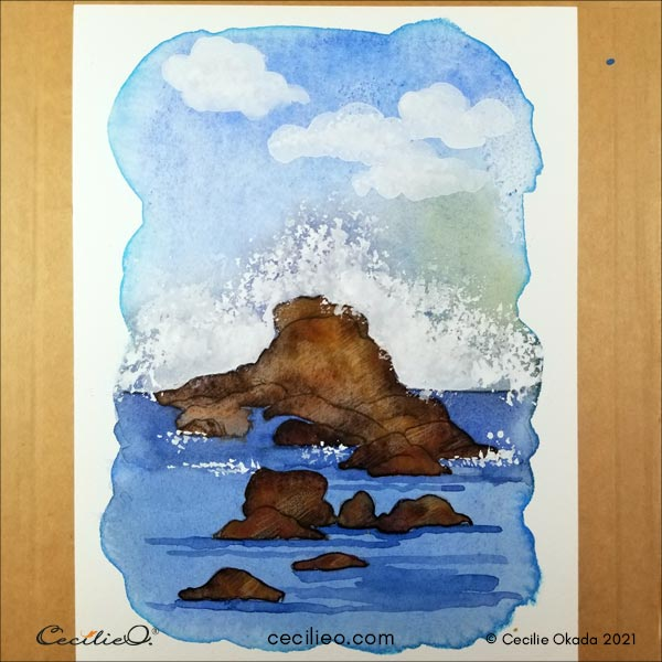 Painting the waves and the clouds with white gouache.