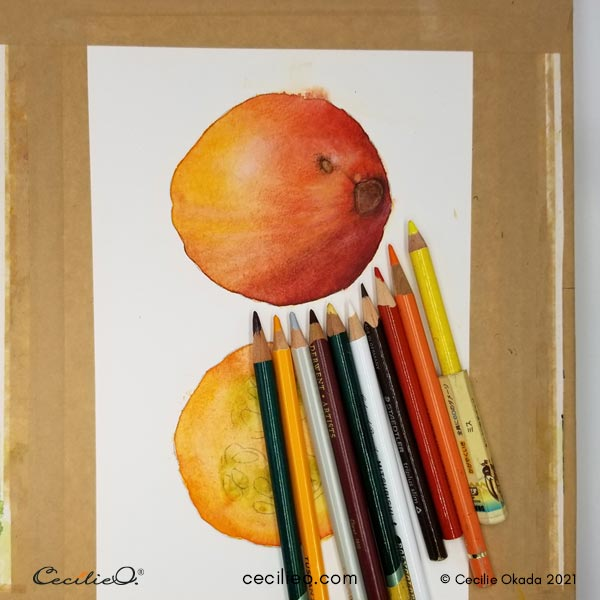 Drawing the details of the pumpkin with colored pencils.