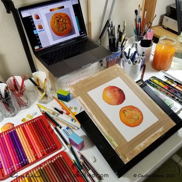 Tilted drawing board on a messy art desk.